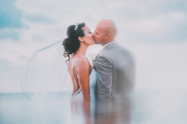 Bride and groom kissing on the beach on their wedding day photo shoot