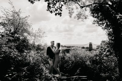 Engaged couple kissing with Bristol suspension bridge in the background