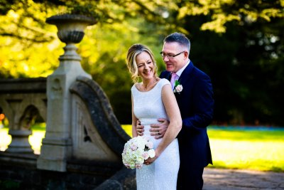 Bride and Groom photo at Insole Court Cardiff under the trees having a sneaky smooch