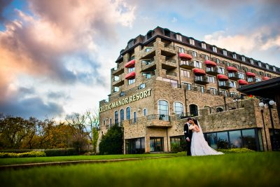 Bride and groom standing in front of the Celtic Manor Hotel on there wedding day photo shoot