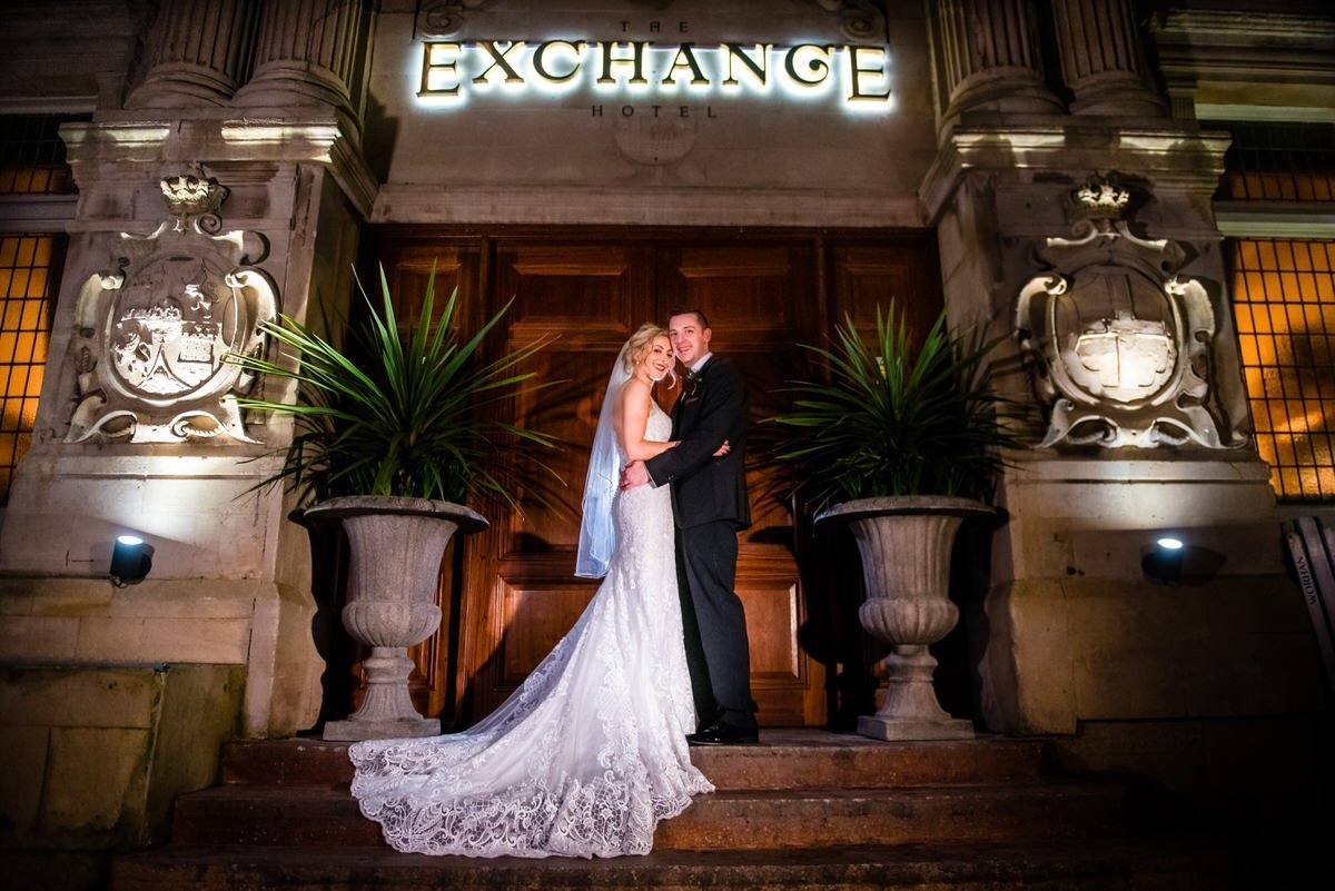 bride and her groom standing at the Exchange Hotle entrance on their wedding day