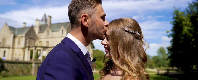Bride and Groom kiss on their wedding day with the wonderful Orchardleigh Estate in the back ground