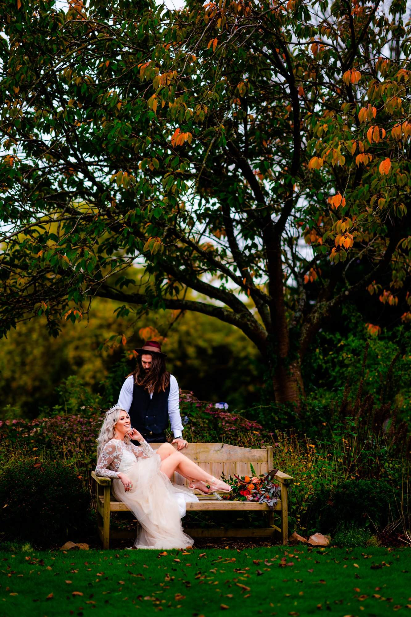 Bride sitting on a bench in the gardens of Miskin Manor