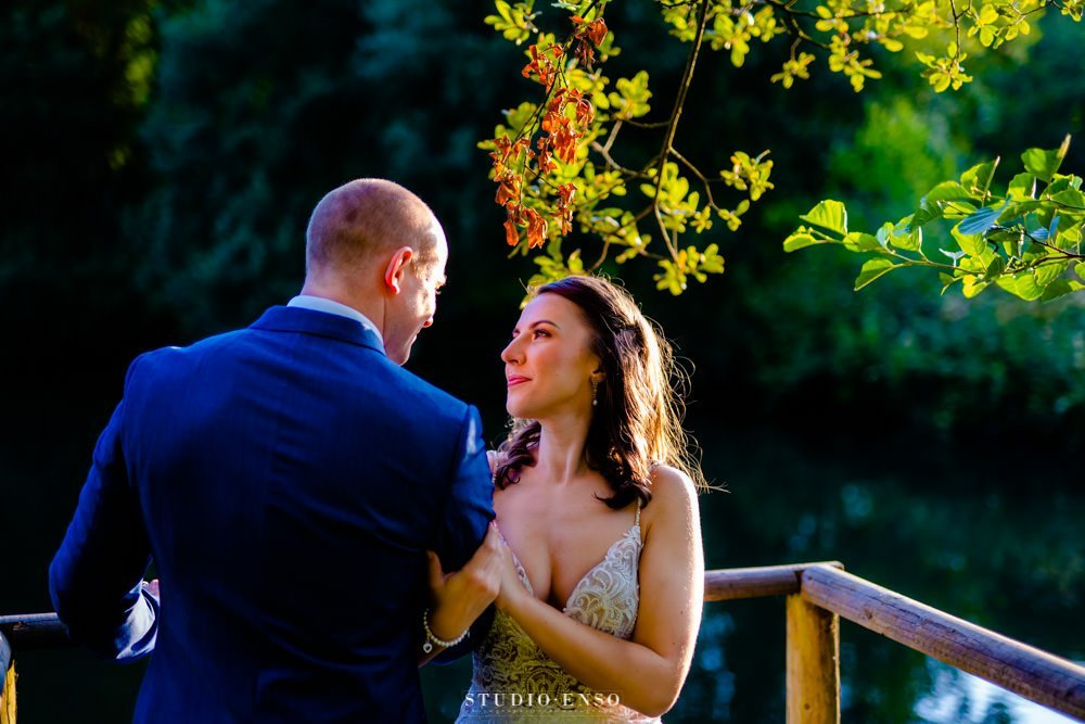 Bride and Groom in front of a lake gazing into eachothers eyes at Llanerch Vineyard on their Wedding day